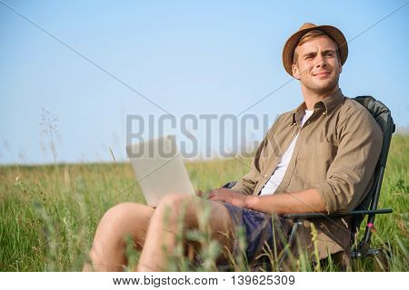 Relaxed young man is enjoying the nature. He is using notebook and looking forward with enjoyment. Tourist is sitting on chair on grass