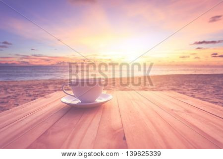 Coffee Cup On Wood Table At Sunset Or Sunrise Beach With Lens Flare. Warm Toning Effect. Retro And V