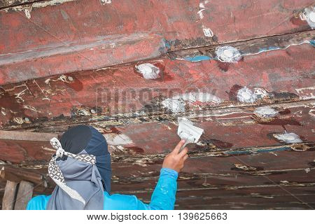 Woman Worker Filling Wood Filler Under Fishing Boat