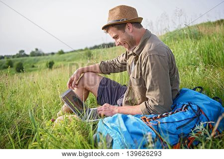 Happy young man is using laptop and smiling. He is sitting on grass near backpack