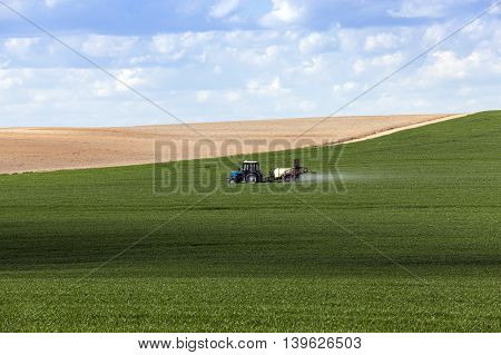 tractor, photographed in the agricultural field during the processing of Pesticides