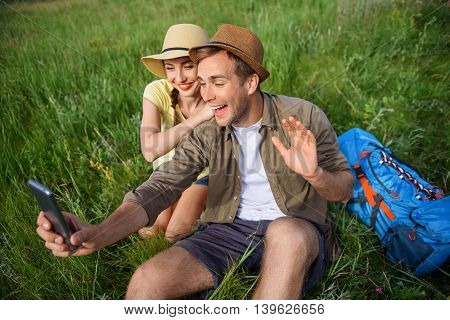 Cheerful loving couple is making selfie on journey. They are sitting on grass and smiling. Man is holding smartphone and waving arm. Woman is embracing him