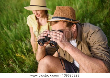 Young tourists are enjoying nature on meadow. Man is sitting on grass and looking into binoculars with interest. Woman is smiling