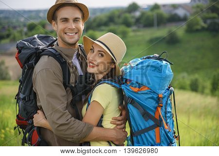 Joyful young man and woman are embracing with love. They are standing on meadow and carrying backpack. Couple is looking at camera and smiling