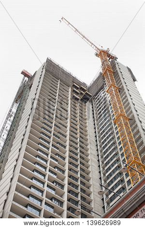 High rise building under construction with crane on site