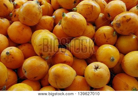 Asian orange loquat fruits piled for market close-up