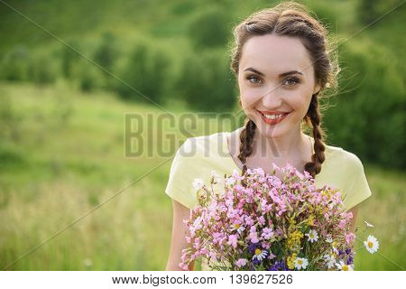 Cheerful girl is holding bouquet and smiling. She is standing on meadow and looking at camera with happiness