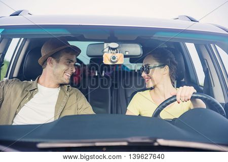 Joyful young loving couple is traveling by car. They are looking at each other