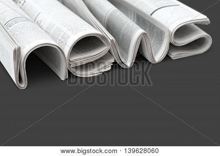 Stacks of modern newspapers composed in form of word NEWS on gray background. Concept of news of world events