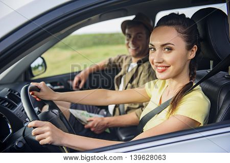 We like traveling. Happy loving couple is sitting in car and smiling. Woman is driving and looking at camera with joy
