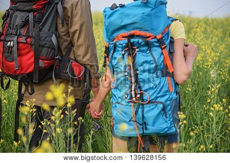 Cheerful tourists are walking in meadow and holding hands. They are carrying backpack. Holding on their back