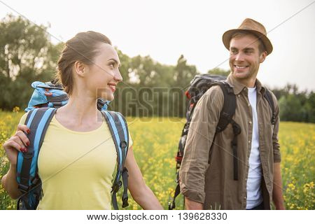 Young man and woman are relaxing on trip. They are walking on meadow and holding hands. Couple is looking at each other with love and smiling