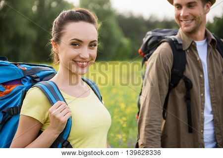 Joyful loving couple is hiking on meadow. They are looking at camera and smiling