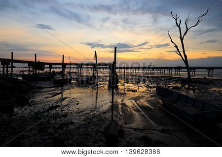 Amazing view of wooden Bridge , jetty and dead tree silhouette in wet land with dramatic sunrise background