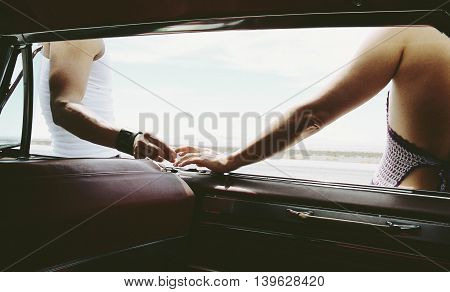 Couple holding hands outside vehicle- from inside.