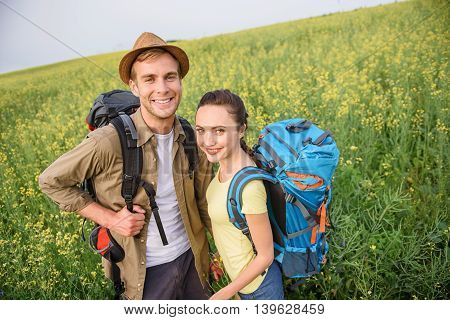 Joyful young tourists relaxing in nature. They are standing on meadow and smiling