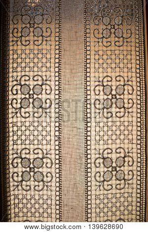 Detail of interior window with intricate lace curtains