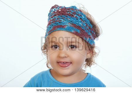 Lovely Kid In Blue Knit Headband Sticking Out Tongue