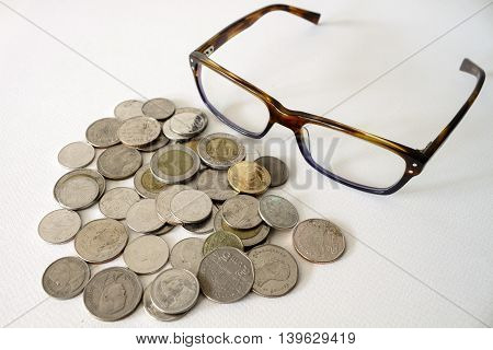 Baht Thai Coins Stacked And Eyeglasses Isolated On White Background.