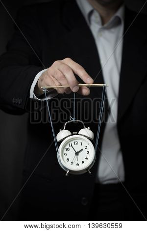 Business man manages a clock hanging on cords and symbolizing the time on dark background