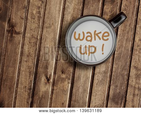 top of view of a cup of milk on wood table with word wake up concept of breakfast