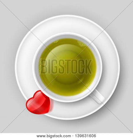 Cup of green tea with red heart on saucer. Top view