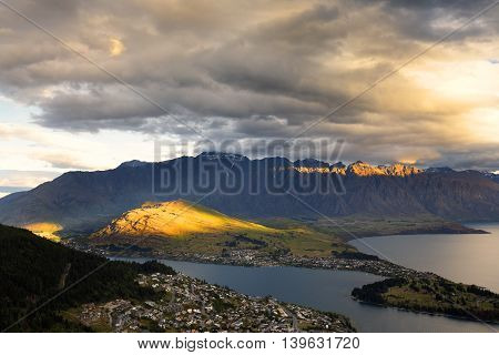 Sun rays is bursting thru thick clouds and illuminate some part of the mountains.