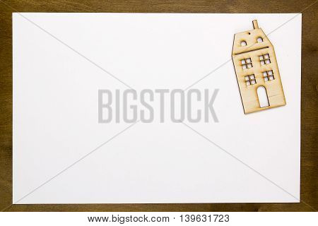 Model home on a white sheet of paper on a wooden table
