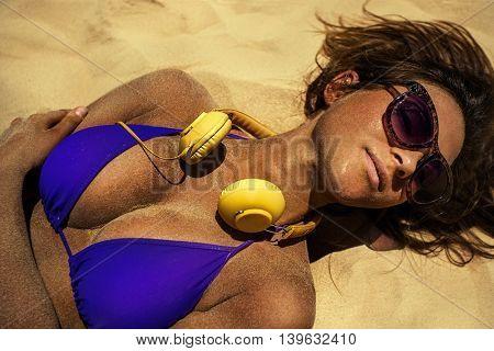 Girl with headphones sunbathing in summertime