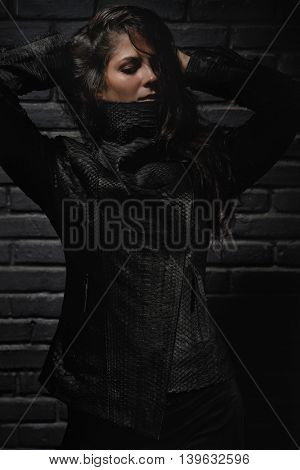 Fashion model posing in reptile leather vest near black brick wall.