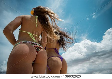 Photo of two girls in bikini on sandy dunes tanning in the bright summer sun