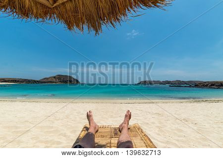 Legs of guy relaxing on sandy beach under umbrella