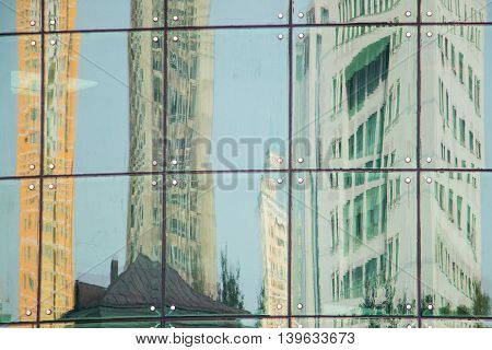 Different colored office buildings reflecting distorted in a glass front