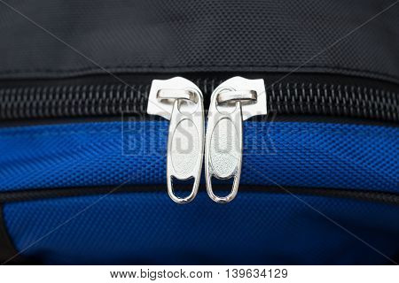 zipper of a blue backpack close up
