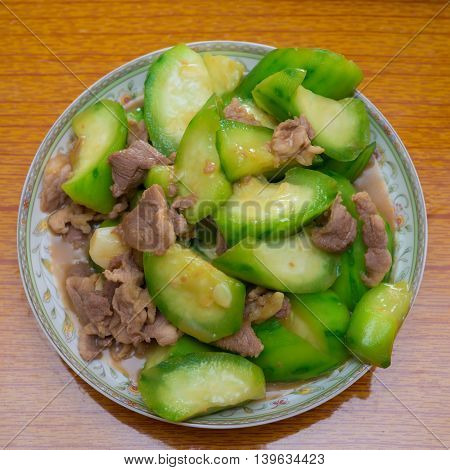 cooked fresh angled loofah with pork on dish ready to eat