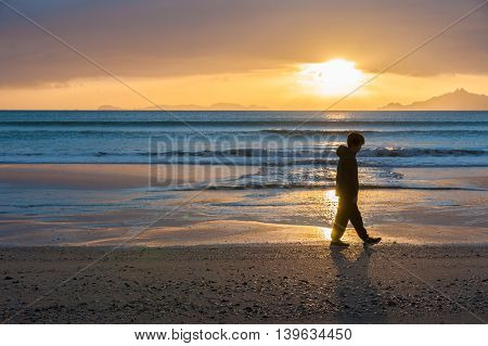 Sunrises glistening across water onto beach as a lone boy walks silhouetted at waters edge and offshore islands seen from Waipu Cove New Zealand.