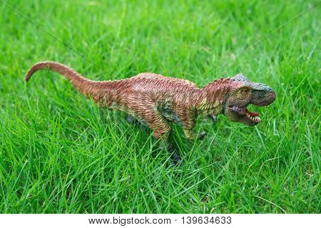 a brown tyrannosaurus toy stands on grass