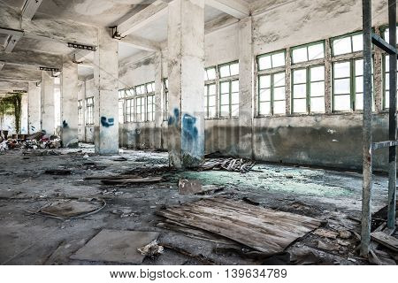abandoned industrial loft in an architectural background with rubbish on floors