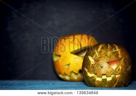 Two spooky pumpkin lanterns in darkness. Blue ang orange. Rustic halloween background. Text space