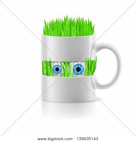 White mug divided into two parts with grass and two eyes inside.