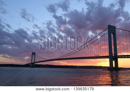 NEW YORK - JULY 23, 2016: Verrazano Bridge at sunset in New York .The Verrazano Bridge is a double-decked suspension bridge that connects the boroughs of Staten Island and Brooklyn