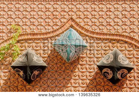 XinjiangChina 09/05/2015 Three traditional Chinese dopa hats attached to an orange wall with decorations throwing a shadow on a sunny day