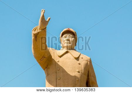 XinjiangChina 09/05/2015 Stone statue of Mao Tse Tung closeup raising his hand to greet his people with a red star on his cap in front of a blue sky on a sunny day