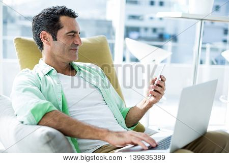 Man using cellphone while sitting with laptop on couch at home