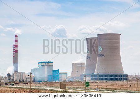 XinjiangChina 09/03/2015 Chinese nuclear power plant with surrounding buildings in front of a blue cloudy sky in Xinjiang China