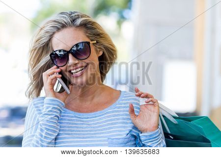 Beautiful woman talking on cellphone while carrying shopping bags on street
