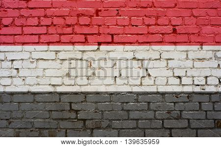 Flag of Yemen painted on brick wall background texture