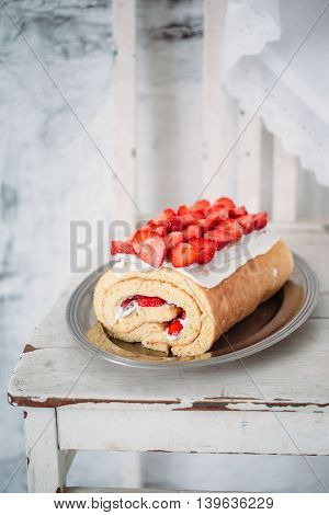 Homemade cake roll with strawberry cream on a white vintage chair
