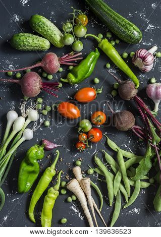 Beets zucchini peppers onion garlic green beans beans tomatoes parsnips cucumbers - fresh vegetables on a dark background. Raw ingredients. Top view;