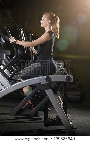 Young woman at the gym exercising. Run on on a machine. Jogging workout in dark fitness club. Cardio.